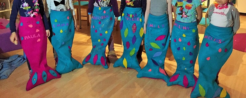Kinder mit selbstgebastelten Meerjungfrauenflossen aus Stoff